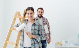 accouplez chaque étreindre à la maison de fixation heureuse neuf l'autre sourire de peinture leur aux outils Photo stock