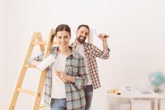 accouplez chaque étreindre à la maison de fixation heureuse neuf l'autre sourire de peinture leur aux outils Photo libre de droits
