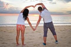 Accouplez effectuer la forme de coeur avec des bras au coucher du soleil Photos libres de droits