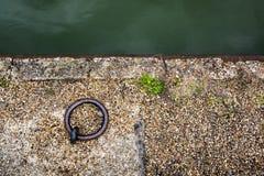Accouplez l'anneau d'ancre sur la banque de canal - fond abstrait Photo stock