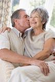 Accouplez la détente dans la salle de séjour embrassant et souriant Images stock