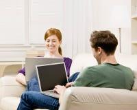 Accouplez la détente dans la salle de séjour tapant sur des ordinateurs portatifs Photos stock