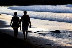 Accouplez la silhouette marchant au bord de la mer au coucher du soleil Photographie stock libre de droits