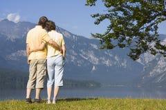 Accouplez le bras dans le bras à un lac de montagne photos stock