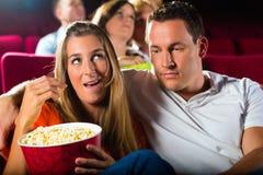 Accouplez le film de observation à la salle de cinéma et maïs éclaté de consommation Photos stock