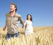 Accouplez le fonctionnement dans le domaine de blé Photo stock