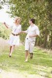 Accouplez le fonctionnement sur des mains et le sourire de fixation de chemin Photographie stock libre de droits