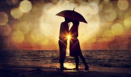 Accouplez les baisers sous le parapluie à la plage dans le coucher du soleil. Photo en o Photo stock