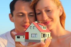 Accouplez maintenir dans le modèle de mains de la maison avec le garage Photographie stock