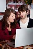 Accouplez regarder dans fixement l'incrédulité à un ordinateur portatif d'ordinateur Photo libre de droits