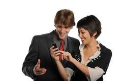 Accouplez regarder un téléphone portable et le sourire Image libre de droits