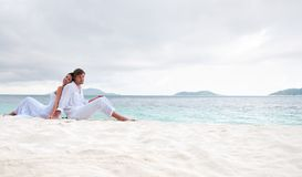 Accouplez se reposer sur la plage près du bord de la mer Image stock
