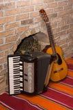 Accoustic-Gitarre auf der Backsteinmauer und dem Akkordeon Lizenzfreies Stockfoto