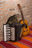 Accoustic guitar on the brick wall and accordion.  Royalty Free Stock Photo