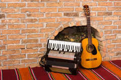 Accoustic guitar on the brick wall and accordion.  Royalty Free Stock Photography