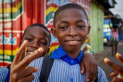 ACCRA, GHANA � MARCH 18: Unidentified African student kids gree. Ting to tourists after school on March 18, 2014 near Nima, Accra, Ghana. Ghana is one of stock images