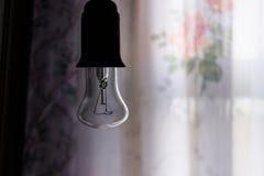 Accrocher a arrêté l'ampoule dans une chambre noire Images libres de droits