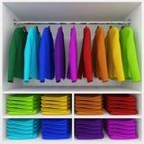Accrocher coloré de vêtements et pile d'habillement dans la garde-robe Photos libres de droits