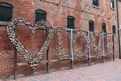 Accrocher coloré ferme à clef sur une barrière d'amour avec un mur rouge à l'arrière-plan à Toronto dans le secteur de distilleri Photographie stock libre de droits