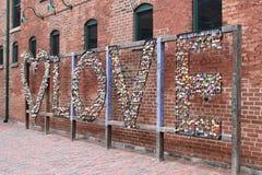 Accrocher coloré ferme à clef sur une barrière d'amour avec un mur rouge à l'arrière-plan à Toronto dans le secteur de distilleri Images libres de droits