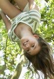 Accrocher de fille à l'envers de l'arbre Photo stock