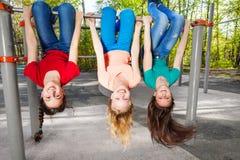 Accrocher de trois filles à l'envers sur la barre brachiating Photographie stock