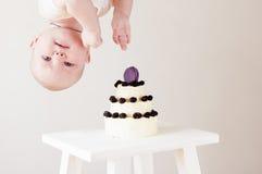 Accrocher nouveau-né drôle à l'envers sur le gâteau photo libre de droits