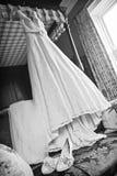 Accrocher renversant de robe de mariage d'un cadre de lit Photo stock