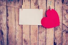 Accrocher rouge et papier sur la corde à linge et corde de coeur avec en bois Image stock