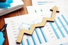 Accroissement d'affaires Flèche en bois et rapports financiers photo stock