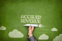 Accrued revenue concept on blackboard with paper plane. Accrued revenue concept on black blackboard with businessman hand holding paper plane Royalty Free Stock Images