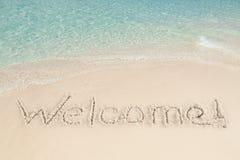 Accueil écrit sur le sable par la mer Photographie stock libre de droits