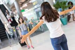 Accueil d'ami de retour par l'aéroport d'embrassement Photographie stock libre de droits