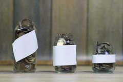Accumulated coins stacked in glass jars Stock Photography