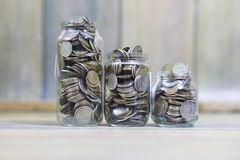 Accumulated coins stacked in glass jars Stock Photos
