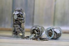 Accumulated coins stacked in glass jars Stock Photo
