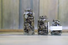 Accumulated coins stacked in glass jars Stock Images