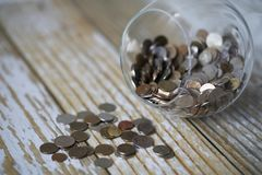 Accumulated coins stacked in glass jars Stock Image