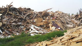 Accumulated waste wood on a field. With its paint and plastic polluting environment Stock Photo
