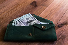 Accumulation. A lot of dollars in the green purse Stock Image