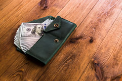 Accumulation. A lot of dollars in the green purse Stock Photography
