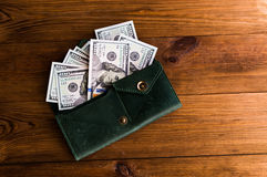 Accumulation. A lot of dollars in the green purse Stock Photo