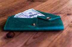 Accumulation. A lot of dollars in the green purse Royalty Free Stock Photography