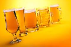 Accumulazione delle tazze di birra con birra Immagine Stock