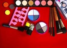 Accumulazione di trucco Ombretto, spazzole di trucco su rosso Fotografia Stock