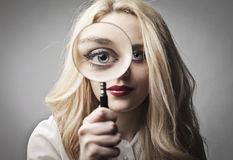 Accuracy. Beautiful woman looking through a magnifying glass Royalty Free Stock Photos