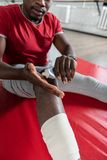 Accurate African American sportsman squeezing healing cream from tube. Treating injury. Accurate African American sportsman squeezing healing cream from tube royalty free stock photo