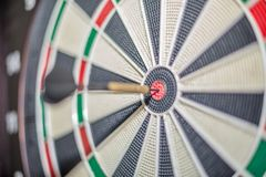 Accurate dart sight hitting center of target, dartboard and dart, blurred background. Trainer focus business goal shooting performance marketing attain accuracy stock images