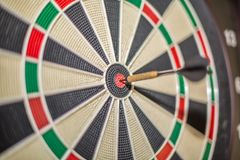 Accurate dart sight hitting center of target, dartboard and dart, blurred background stock image