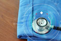 Stethoscope with blue doctor coat on wooden table with shallow D. Accurate diagnosis appropriate treatment medical concept.Doctor hand working with stethoscope Stock Photo